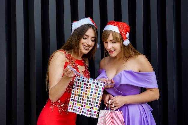 Dwie niesamowite kobiety w mikołajowych czapkach i eleganckich sukniach wieczorowych trzymające torby na zakupy