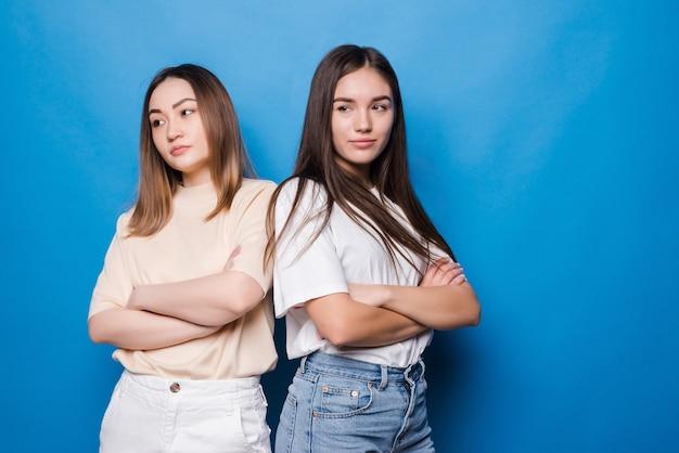 Dwie niezadowolone kobiety pozowanie na białym tle na żółtej niebieskiej ścianie. koncepcja stylu życia ludzi. makieta miejsca na kopię. trzymając się za ręce skrzyżowane