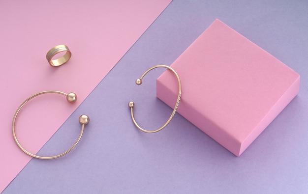 Dwie nowoczesne bransoletki i potrójny pierścionek na różowym i fioletowym tle z miejscem na kopię