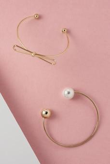 Dwie nowoczesne złote bransoletki na różowej powierzchni