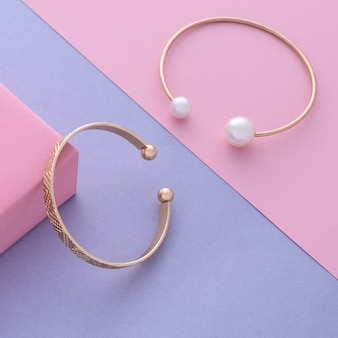 Dwie nowoczesne złote z perłą i klasyczne bransoletki na ukośnym pastelowym tle