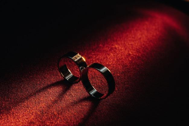 Dwie obrączki na czerwonej powierzchni. złote obrączki zakochanej pary. pojęcie miłości. obrączka ślubna.
