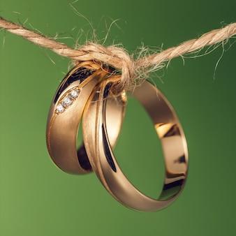Dwie obrączki ślubne związane sznurem na zielonym tle