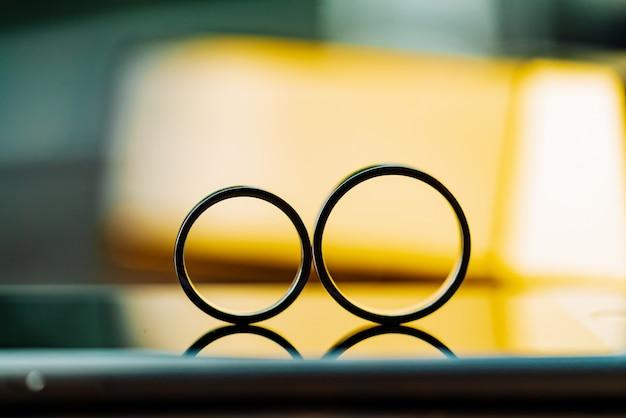 Dwie obrączki. złote pierścienie w postaci ośmiu lub nieskończonych są przeznaczone dla pary młodej. zbliżenie