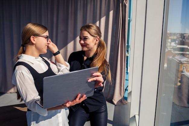 Dwie odnoszące sukcesy architektki rozmawiają o wspólnym projekcie stojąc przy oknie z laptopem. młode ekonomistki, ubrane w formalne stroje, rozmawiające podczas przerwy w pracy