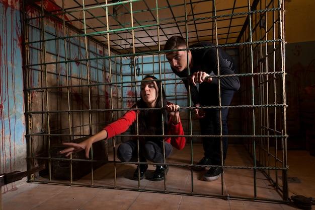Dwie ofiary halloween uwięzione w metalowej klatce z zakrwawioną ścianą za nimi, dziewczyna wyciąga rękę przez kraty i próbuje się wydostać