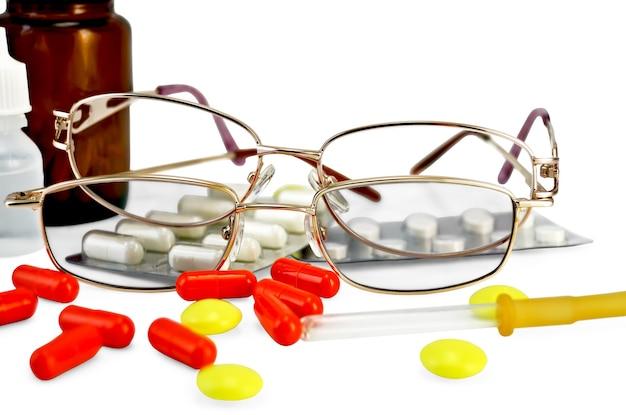 Dwie okulary, kapsułka, tabletki, dwie butelki leku, odizolowana pipeta