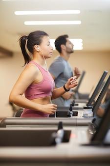 Dwie osoby biegające na bieżni w siłowni