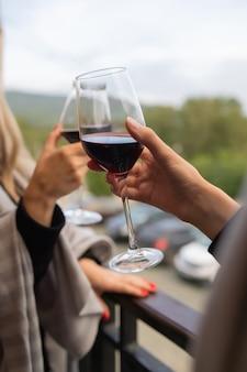 Dwie osoby brzęczące kieliszkami czerwonego wina, świętujące sukces lub mówiące toastem w winiarni, na stojakach z butelkami wina, z bliska.