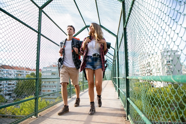 Dwie osoby idą na most otoczony zieloną siatką. kaukaski mężczyzna i kobieta niosąc plecaki i idąc ścieżką. koncepcja turystyki z plecakiem, przygody i wakacji letnich