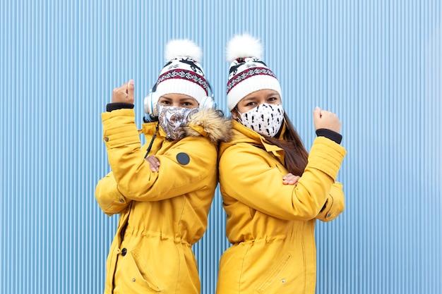 Dwie osoby noszące maski na twarz i zimowe ubrania na białym tle na niebieskim tle.