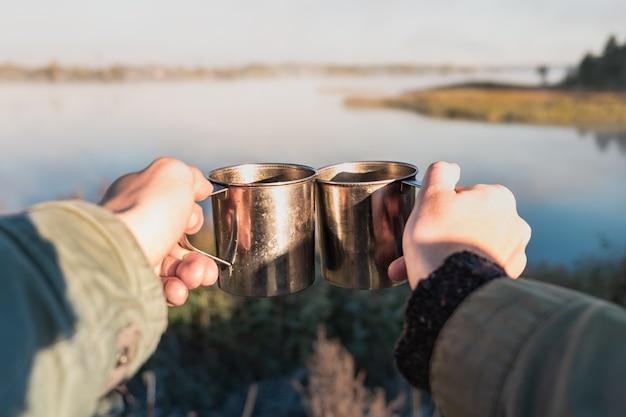 Dwie osoby o poranku piją gorące napoje w rzece. przyjaźń, koncepcja partnerów: dzielenie się wspaniałą chwilą w pięknym miejscu.