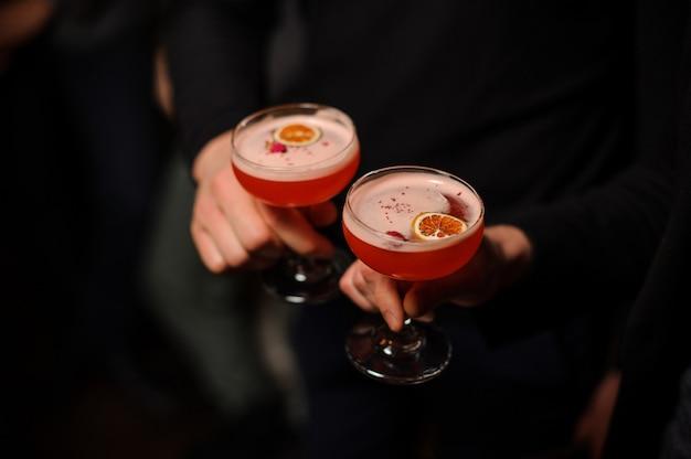 Dwie osoby posiadające kieliszki koktajlowe ze słodkim napojem alkoholowym
