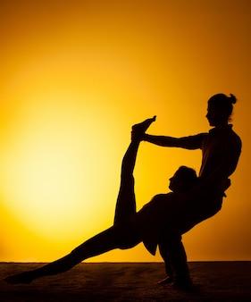 Dwie osoby praktykujące jogę w świetle zachodzącego słońca