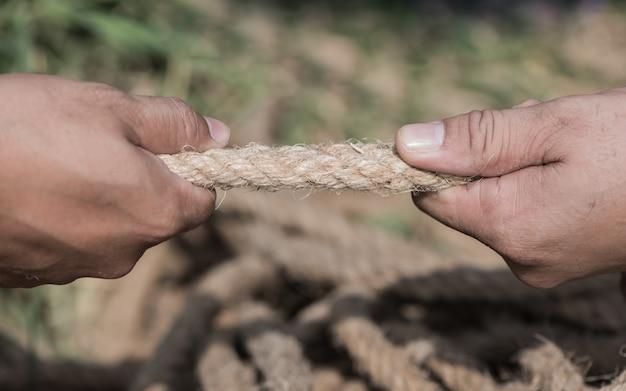 Dwie osoby ręcznie ciągnąc linę.