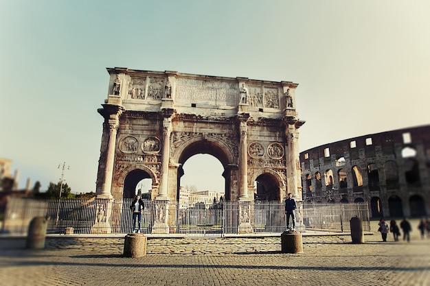 Dwie osoby stojące na kolumnach niedaleko łuku konstantyna