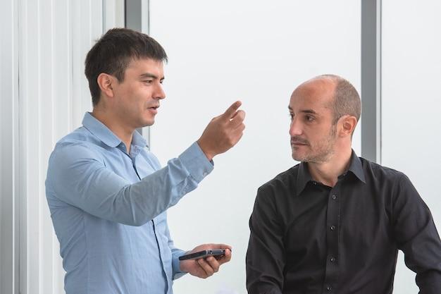 Dwie osoby szukające na smartfonie handlu online