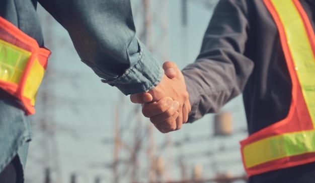 Dwie osoby uścisk dłoni współpraca zespołowa inżynier nadzorca brygadzista