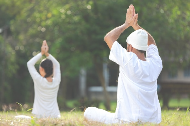 Dwie osoby w białym stroju medytujące na łonie natury