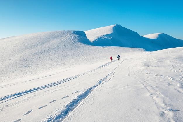 Dwie osoby w pięknych zimowych górach. śnieżny krajobraz