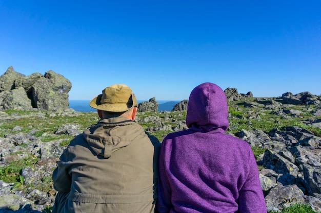 Dwie osoby w podróżnych ubraniach siedzą w górskim krajobrazie