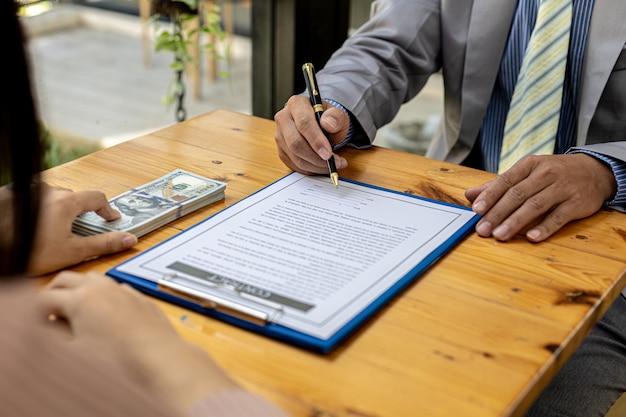 Dwie osoby zachowują się korupcyjnie, są wspólnymi partnerami biznesowymi i podpisują umowy o łapówki dla obopólnych korzyści. pojęcie oszustwa biznesowego i przekupstwa jest nielegalne.