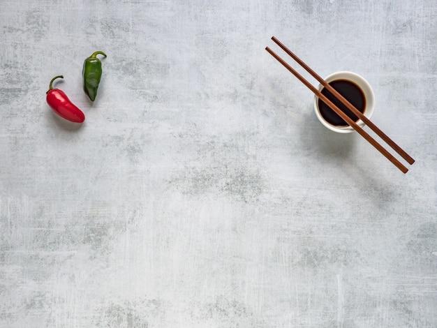 Dwie ostre papryki i sos sojowy z pałeczkami.
