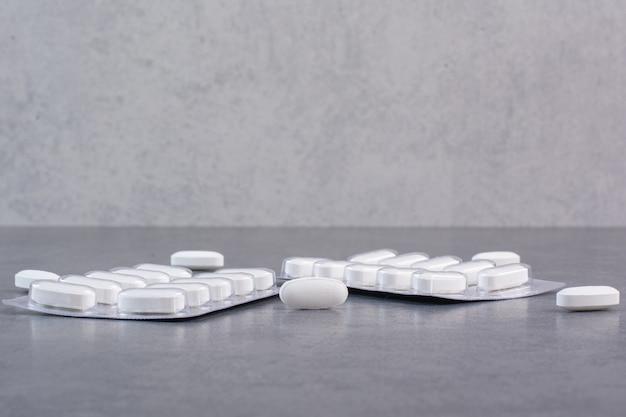 Dwie paczki białych tabletek na marmurowym stole.