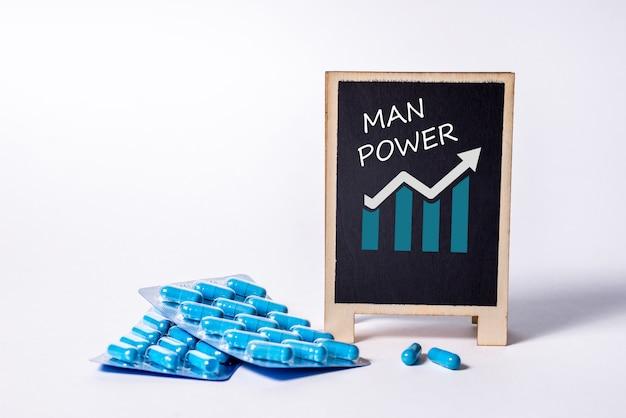Dwie paczki niebieskich kapsułek i słowo moc człowieka na tablicy. tabletki na zdrowie mężczyzn i energię seksualną. pojęcie erekcji, potencji. leczenie męskiej niepłodności i impotencji.