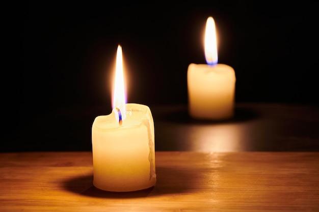 Dwie palące się świece na stole w nocy