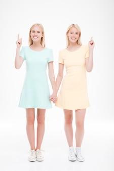 Dwie panie trzymając się za ręce. pojedynczo na białej ścianie. patrząc na przód. wskazują palcami.