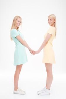 Dwie panie trzymając się za ręce. pojedynczo na białej ścianie. patrząc na przód.