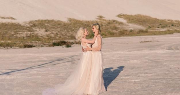 Dwie panny młode kobiety w białej sukni z blond włosami przytulające się, lesbijskie wesele