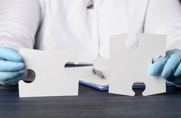 Dwie papierowe, białe puzzle w dłoni lekarza, miejsce na napis, z bliska