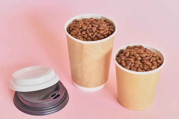Dwie papierowe filiżanki do kawy z ziaren kawy