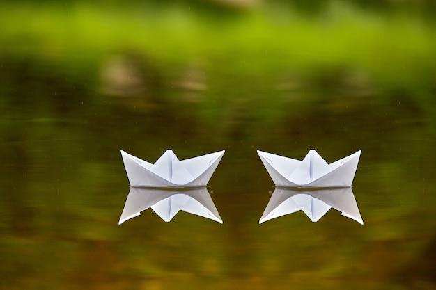 Dwie papierowe łódki z wodą jako symbol romansu i przyjaźni.