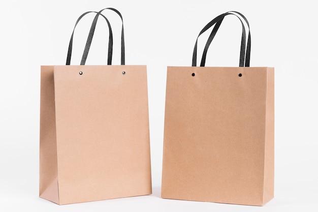 Dwie papierowe torby na zakupy z czarnymi uchwytami