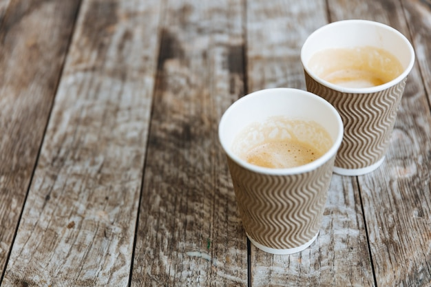 Dwie papierowe, żebrowane kubki świeżo zaparzonego aromatycznego cappuccino z bujną mleczną pianką na drewnianym stole