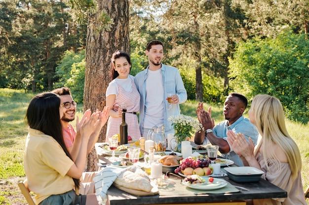 Dwie pary młodych randek międzykulturowych klaszczą w dłonie i gratulują zakochanej parze rasy kaukaskiej zaręczyn przy kolacji