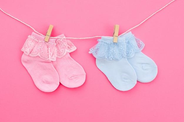 Dwie pary niebieskie i różowe słodkie skarpetki dziecięce wiszące na sznurku na różowym tle. akcesoria dla niemowląt. leżał płasko.