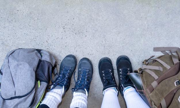 Dwie pary nóg w butach do wędrówek stoją na szarym chodniku z plecakami.
