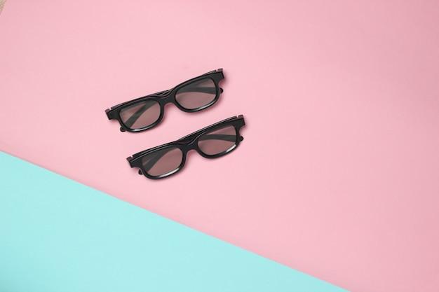 Dwie pary okularów 3d na różowej niebieskiej pastelowej powierzchni. widok z góry. minimalizm