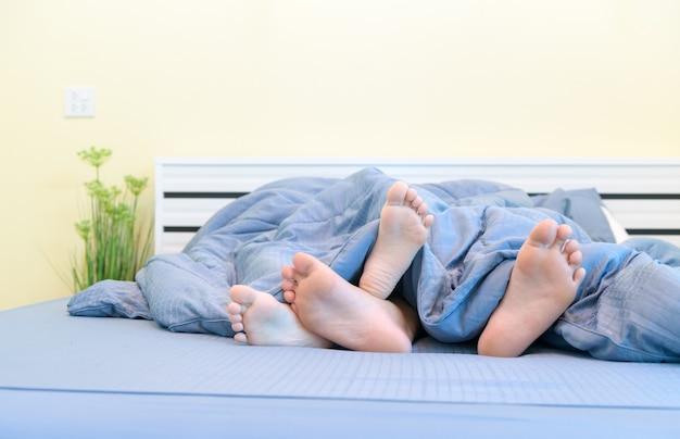 Dwie pary stóp dzieci pod kocem w łóżku,