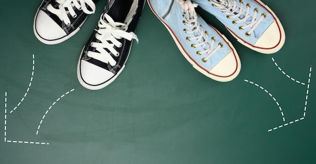 Dwie pary tekstylnych sneakersów skierowane są w przeciwnych kierunkach. koncepcja kłótni i różnicy zdań, różne ścieżki życiowe i zainteresowania, widok z góry