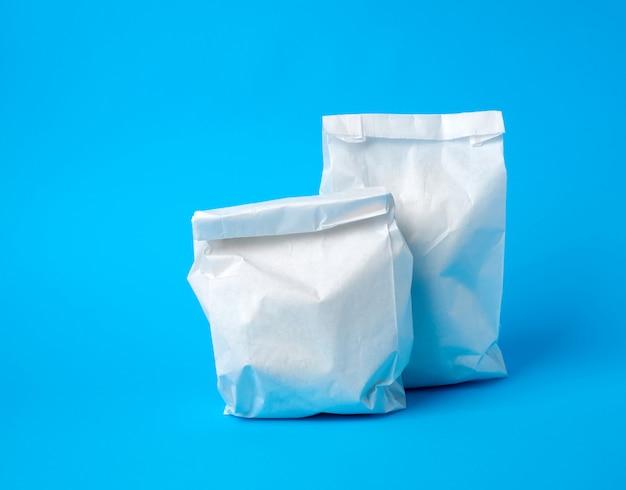 Dwie pełne papierowe jednorazowe torby na żywność na niebieskiej przestrzeni