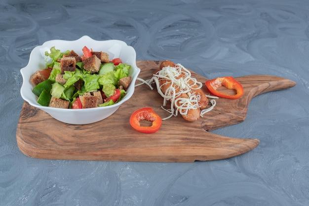 Dwie pieczone kiełbaski z tartym serem i przyozdobione kawałkami pieprzu obok salaterki na desce na marmurowym stole.
