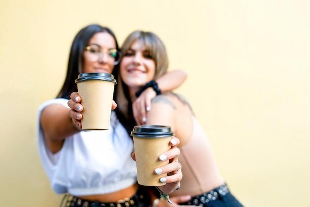 Dwie piękne 20-letnie letnie dziewczyny w różnokolorowych sukienkach, uśmiechając się do kamery i pokazując na białym tle papierowe kubki z kawą na żółtym tle