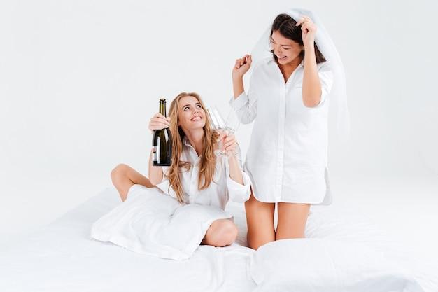 Dwie piękne atrakcyjne kobiety świętujące ślub z butelką szampana noszącą welon