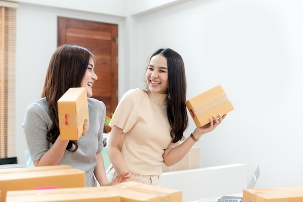 Dwie piękne azjatki podnoszą karton. z radosną, uśmiechniętą twarzą, będąc nowym, normalnym biznesem online
