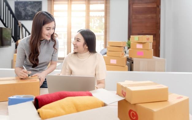 Dwie piękne azjatki sprawdzają zamówienia na laptopach przez internet.